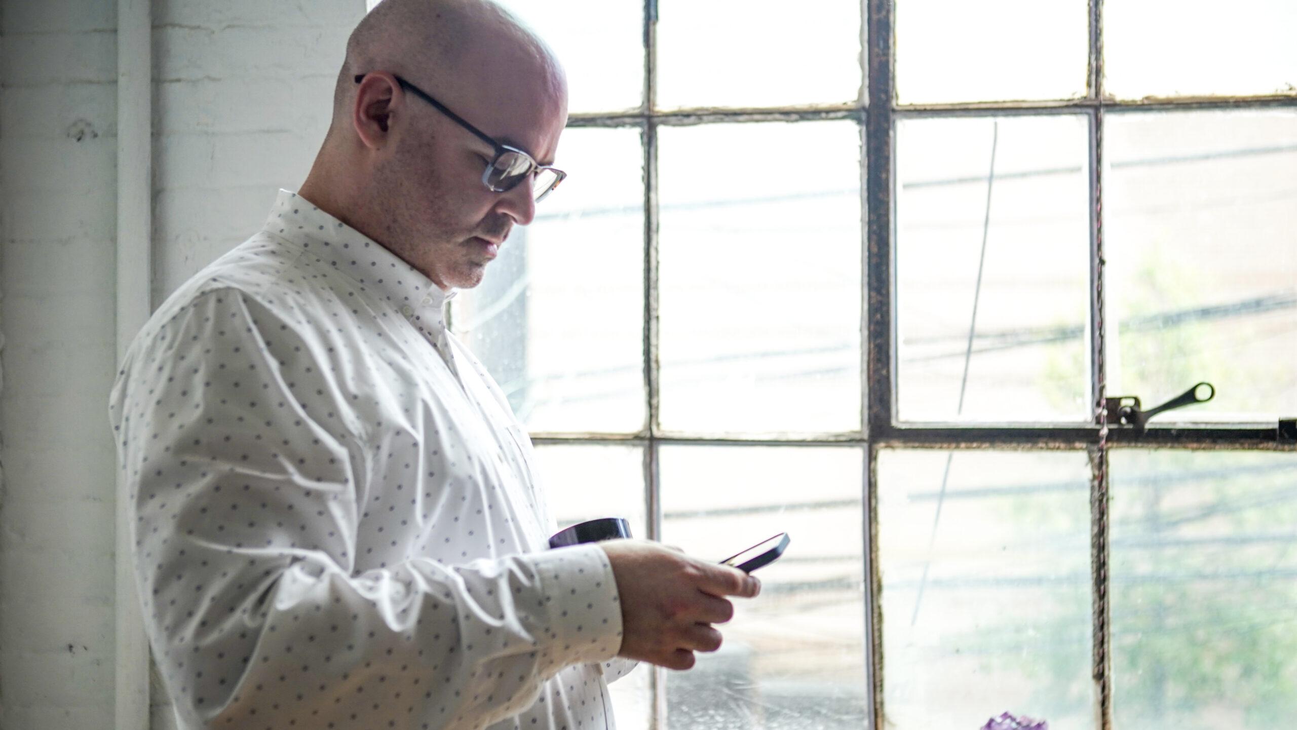 Jay Mandel looking at phone